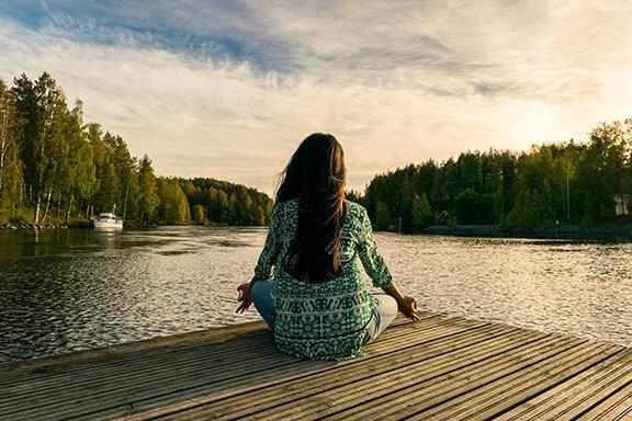 Frau sitzt am See und meditiert