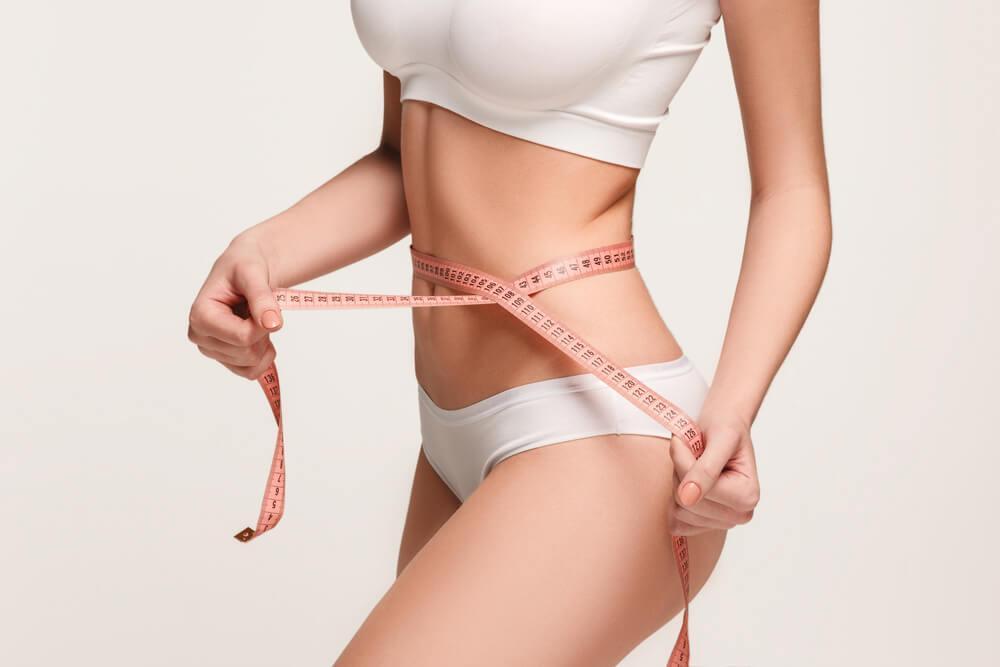 Bild vom Körper einer Frau, die ein Maßband um ihre Taille hält