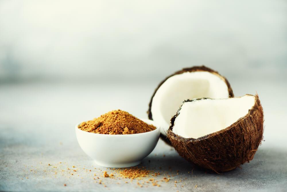 kokoszucker in einer kleinen Schale, nebendran eine aufgeschnittene Kokosfrucht