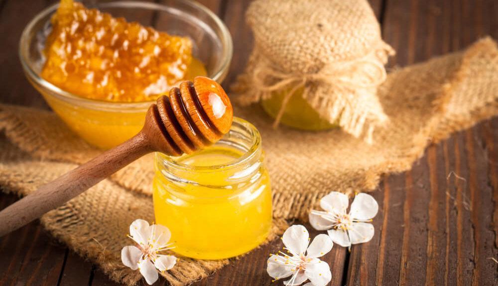 Honigglas mit Honiglöffel und Blumen verziert