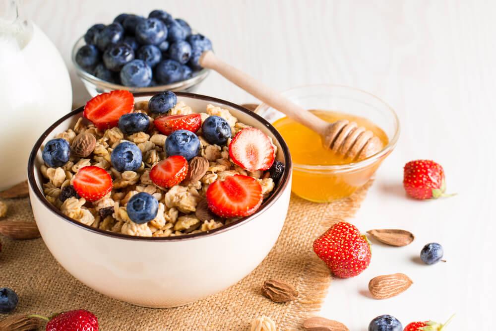 Früstücksschale mit Müsli, Früchten und Honig verziert