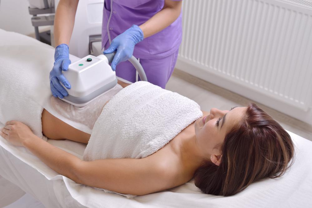 Frau hat Applikator auf ihrem Bauch zur Fettreduktion