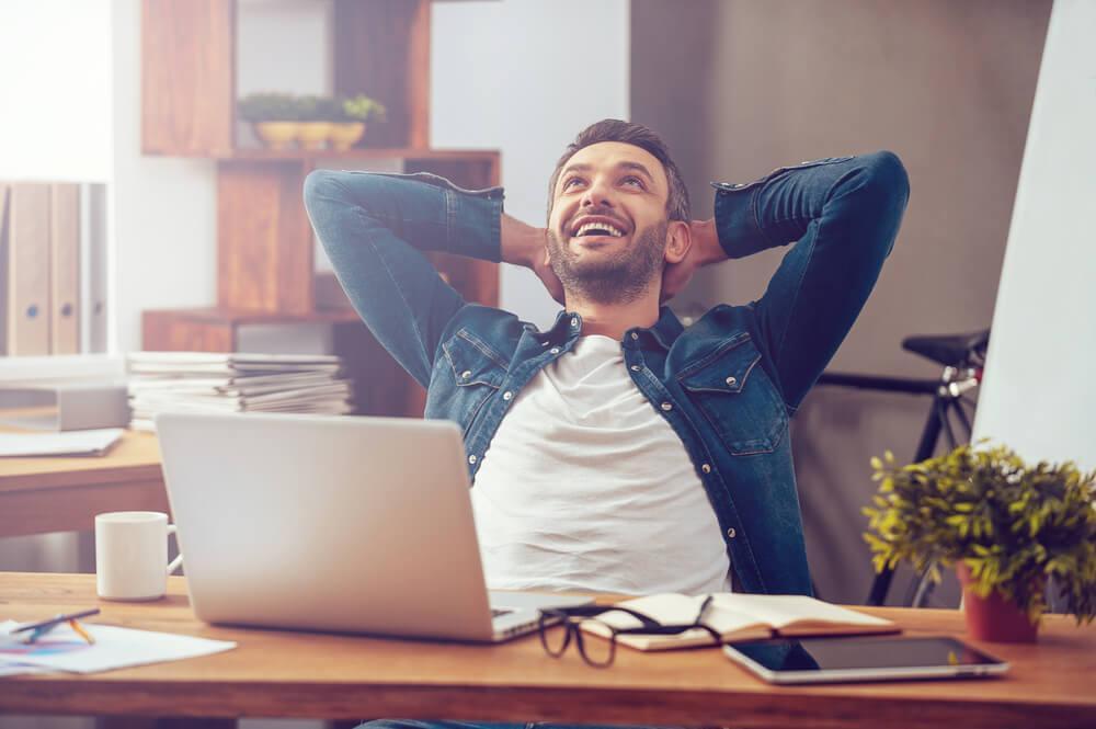 Mann sitzt am Schreibtisch auf der Arbeit und lächelt in entspannter Pose