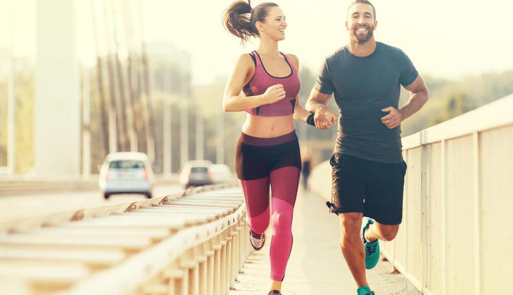 Mann und Frau joggen auf Brücke