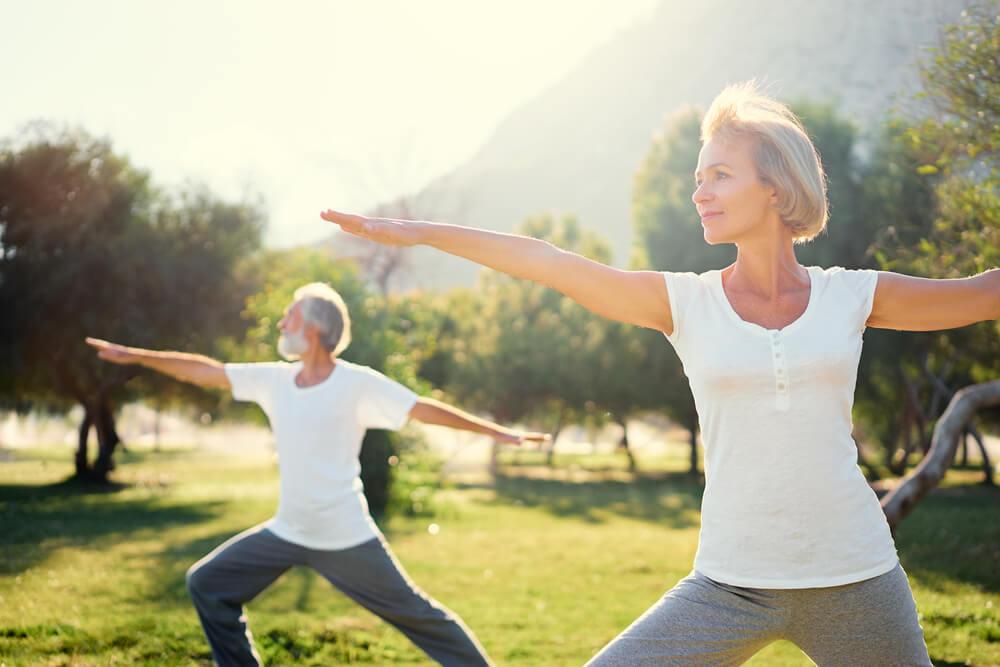 Ältere Frau und Mann machen Yoga auf der Wiese
