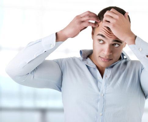 Junger Mann greift sich an die Haare (an Geheimratsecken)