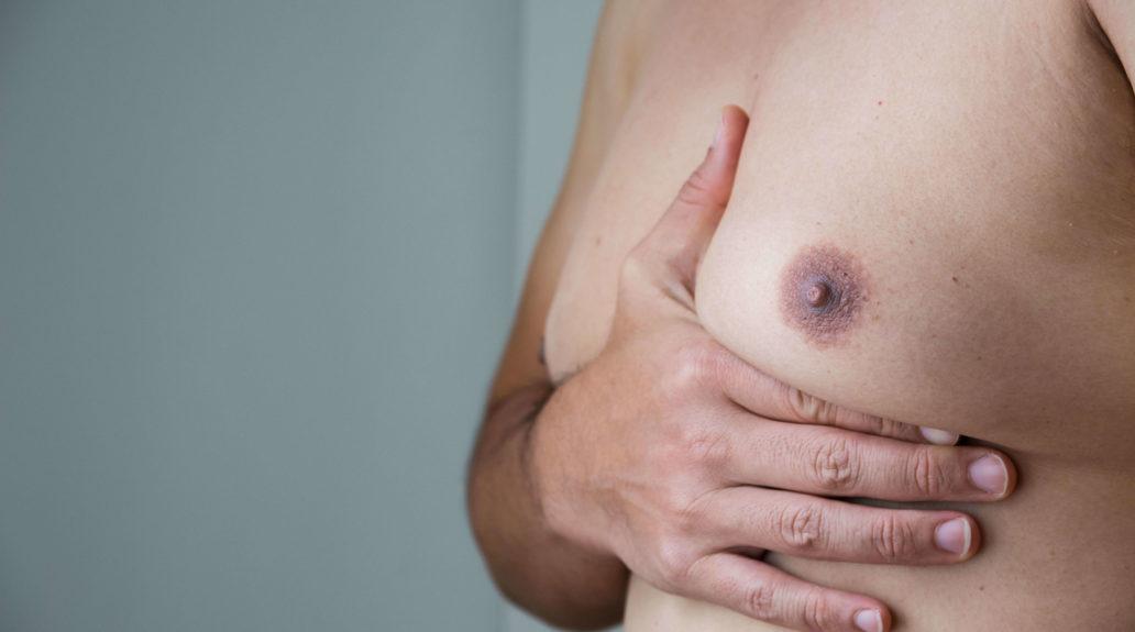 Mann mit freiem Oberkörper hält seine vergrößerte Brust mit der Hand
