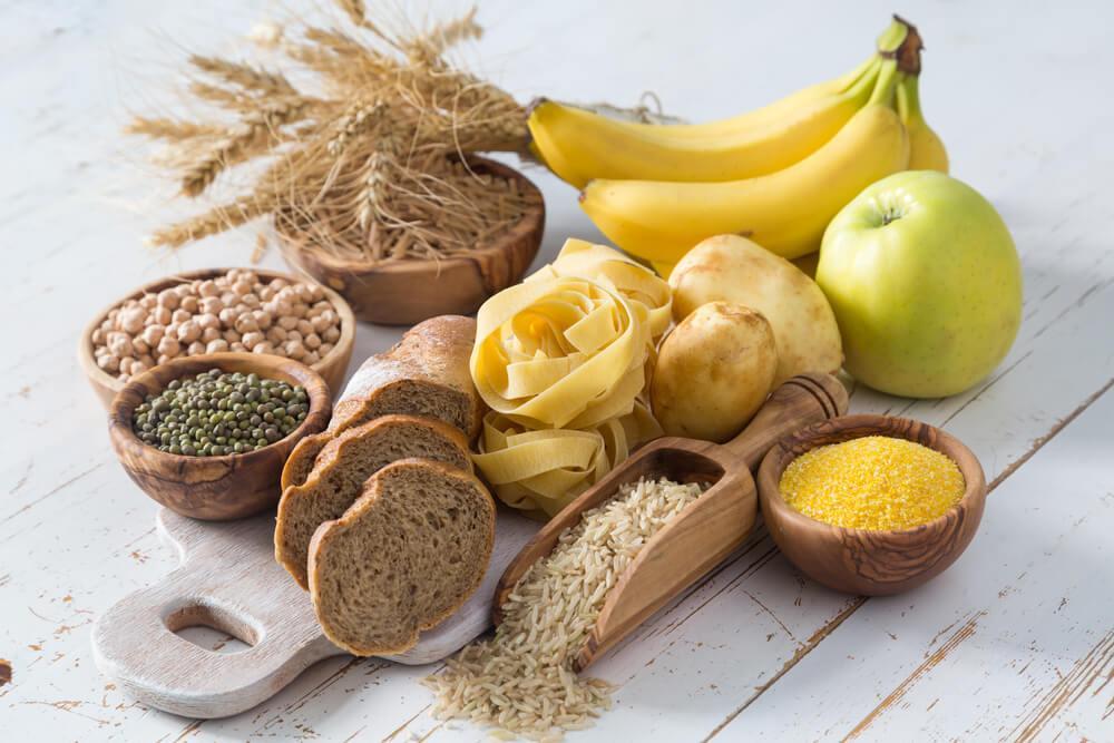 Tisch mit Getreide, Nudeln und diversen Früchten wie Apfel und Banane