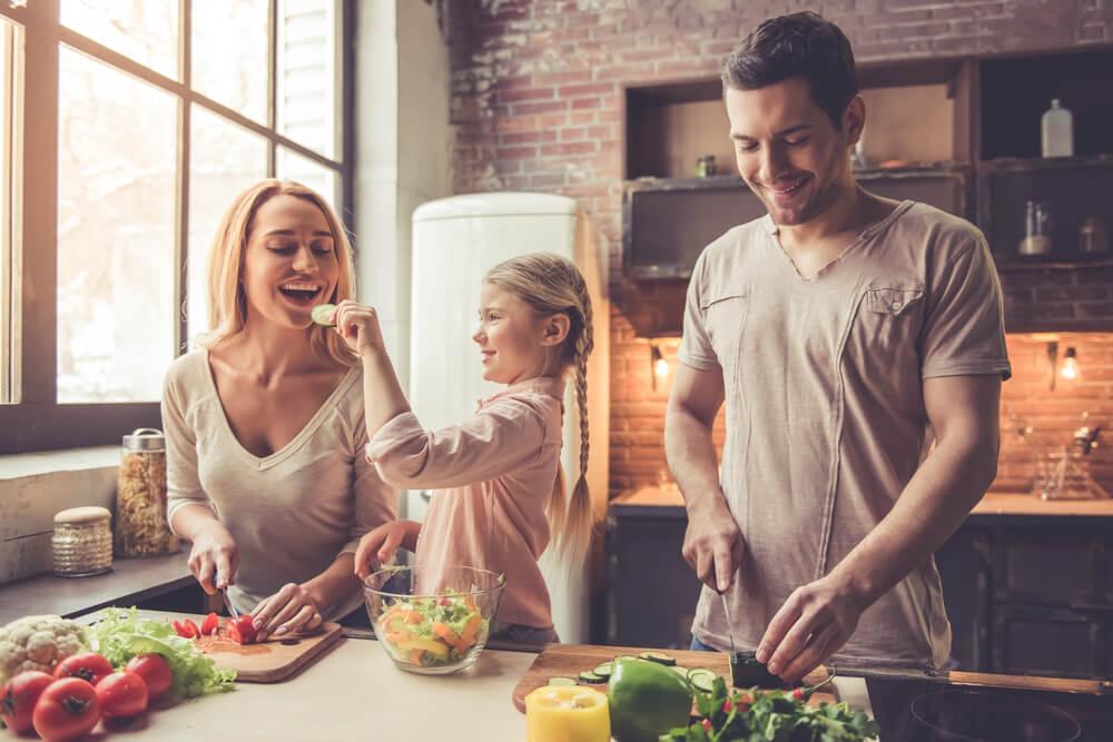 Eine Familie aus Mutter, Vater und Tochter kochen zusammen in der Küche