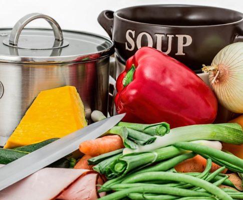Bild von Gemüse mit Topf und Messer auf einem Tisch