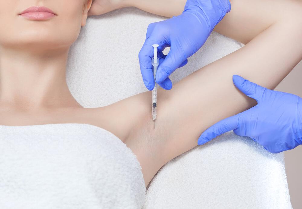 Frau lässt sich Botox mit Spritze in die Achselhöhle injizieren