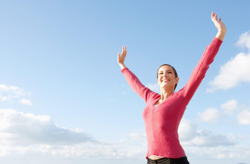 Frau streckt freudig Arme in die Luft